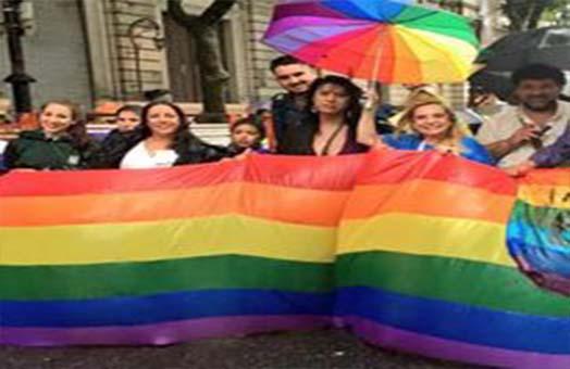 Maria Jose Lubertino junto a otras personas marchando por los derechos LGTTTBIQ tomando una bandera con los colores de la diversidad