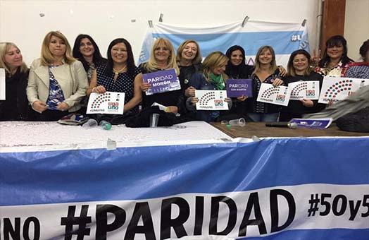Grupo de mujeres luchando por la paridad en la toma de decisiones entre mujeres y varones