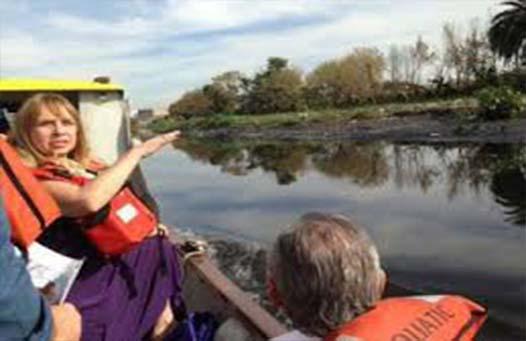 María José Lubertino junto a otras personas navegando el riachuelo analizando su sanación